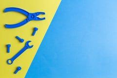 Gioca la priorità bassa La costruzione dei bambini gioca gli strumenti su fondo blu e giallo Vista superiore Immagine Stock