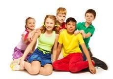 Giocando i bambini che si siedono insieme sul pavimento Immagini Stock