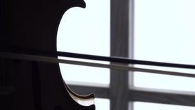 Giocando la fine del violoncello su contro la finestra Fine in su stock footage