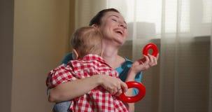 Giocando a mamme con il ragazzo del bambino con i blocchi ed i giocattoli colorati della piramide stock footage
