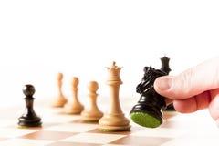 Giocando scacchi - pezzi degli scacchi commoventi di una mano su una scacchiera Fotografia Stock Libera da Diritti