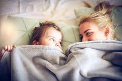 Giocando sotto la coperta con la mamma Piccola ballerina immagini stock libere da diritti