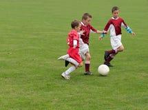 Giocar a calcioe dei bambini Immagini Stock