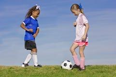 Giocar a calcioe di due ragazze Immagine Stock