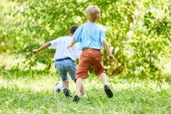 Giocar a calcioe sportivo di due ragazzi fotografie stock