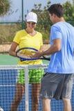 Giocar a tennise o lezione delle coppie della donna dell'uomo Fotografia Stock