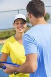 Giocar a tennise o lezione delle coppie della donna dell'uomo Immagine Stock
