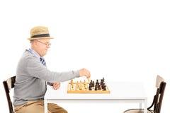 Giocare senile dell'uomo anziano degli scacchi da solo Immagini Stock Libere da Diritti