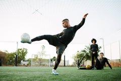 Giocatore che dà dei calci al pallone da calcio sul campo Immagini Stock