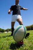 Giocatore che dà dei calci alla palla di rugby sul campo erboso Fotografie Stock Libere da Diritti