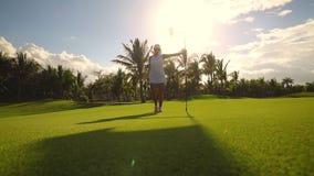 Giocatore del campione e del campo da golf vicino al foro con la bandiera, località di soggiorno tropicale di lusso archivi video