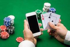 Giocatore del casinò con le carte, lo smartphone ed i chip Immagini Stock