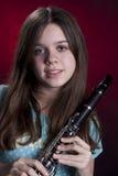 Giocatore del Clarinet dell'adolescente su colore rosso Immagine Stock