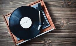 Giocatore del vinile con le piastrine su una tavola di legno Spettacolo 70s Ascolti musica Fotografie Stock Libere da Diritti