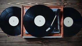 Giocatore del vinile con le piastrine su una tavola di legno Spettacolo 70s Ascolti musica Immagini Stock Libere da Diritti