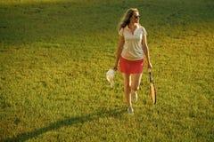 Giocatore della donna con la passeggiata della racchetta di tennis su prato inglese Fotografia Stock