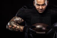 Giocatore dello sportivo di football americano isolato su fondo nero immagine stock libera da diritti