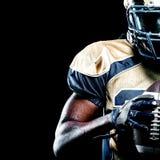 Giocatore dello sportivo di football americano isolato su fondo nero fotografia stock