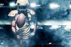 Giocatore dello sportivo di football americano su funzionamento dello stadio nell'azione Fotografia Stock Libera da Diritti