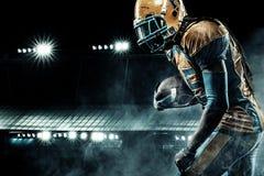 Giocatore dello sportivo di football americano su funzionamento dello stadio nell'azione fotografie stock libere da diritti