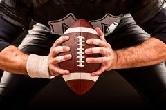 Giocatore dello sportivo di football americano sullo stadio con le luci su fondo nero fotografia stock libera da diritti