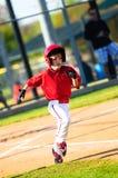 Funzionamento del giocatore di baseball della piccola lega Immagine Stock