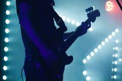 Giocatore di basso elettrico alle luci blu della fase Fotografie Stock Libere da Diritti