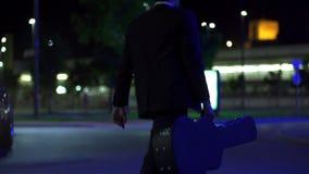 Giocatore di chitarra che cammina attraverso la via davanti alla corvetta blu al rallentatore stock footage