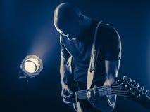Giocatore di chitarra davanti al tono del blu del riflettore Fotografie Stock