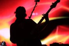 Giocatore di chitarra della siluetta con gli ambiti di provenienza variopinti Fotografie Stock