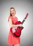 Giocatore di chitarra femminile contro la pendenza Immagine Stock