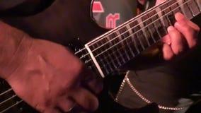 Giocatore di chitarra in scena ad un concerto che oscilla il pubblico stock footage