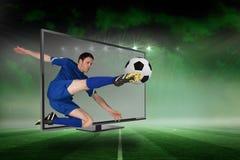 Giocatore di football americano adatto che dà dei calci alla palla attraverso la TV Fotografia Stock Libera da Diritti