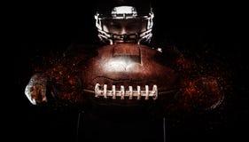 Giocatore di football americano, atleta in casco con la palla su fondo nero Carta da parati di sport con copyspace fotografia stock
