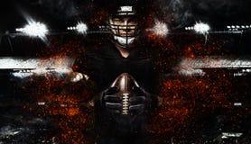 Giocatore di football americano, atleta in casco con la palla su fondo nero Carta da parati di sport con copyspace immagine stock