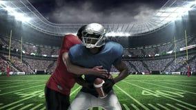 Giocatore di football americano che affronta per la palla video d archivio