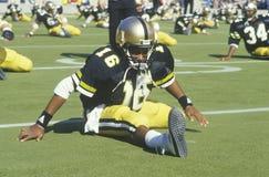 Giocatore di football americano che allunga sul campo Fotografia Stock