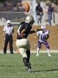 Giocatore di football americano che dà dei calci ad una palla Fotografie Stock Libere da Diritti