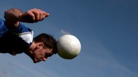Giocatore di football americano che dirige la palla sotto il cielo blu stock footage