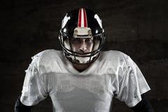 Giocatore di football americano che esamina macchina fotografica su fondo concreto fotografia stock libera da diritti