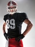 Giocatore di football americano che posa con la palla su fondo bianco fotografia stock libera da diritti