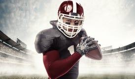 Giocatore di football americano che posa con la palla sul fondo dello stadio fotografie stock