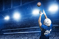 Giocatore di football americano che prende un passaggio di atterraggio immagini stock libere da diritti