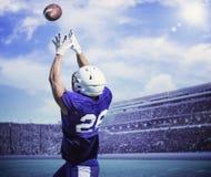 Giocatore di football americano che prende un passaggio di atterraggio immagine stock libera da diritti