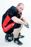 Giocatore di football americano che si siede sul casco Fotografia Stock