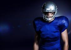 Giocatore di football americano che sta contro il fondo blu fotografia stock