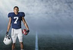 Giocatore di football americano che sta in uno stadio alla notte Fotografie Stock Libere da Diritti