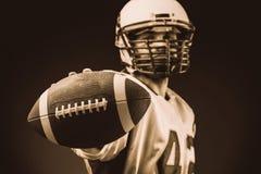 Giocatore di football americano che tiene la palla in sue mani davanti alla macchina fotografica Football americano di concetto,  fotografia stock libera da diritti