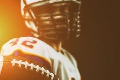 Giocatore di football americano che tiene la palla in sue mani davanti alla macchina fotografica Football americano di concetto,  fotografia stock