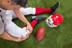 Giocatore di football americano con la lesione in gamba fotografie stock